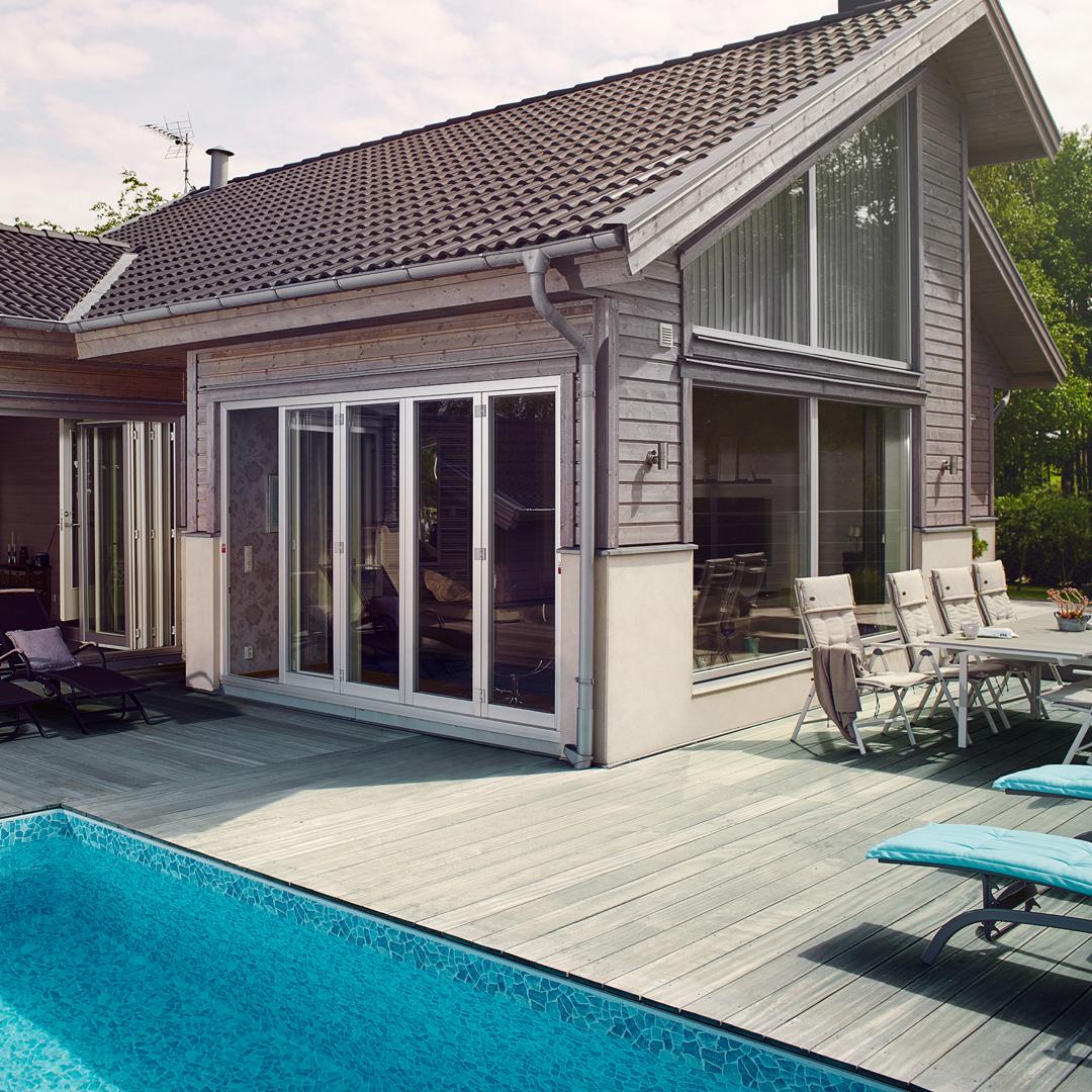 hus med terrasse og basseng i hagen