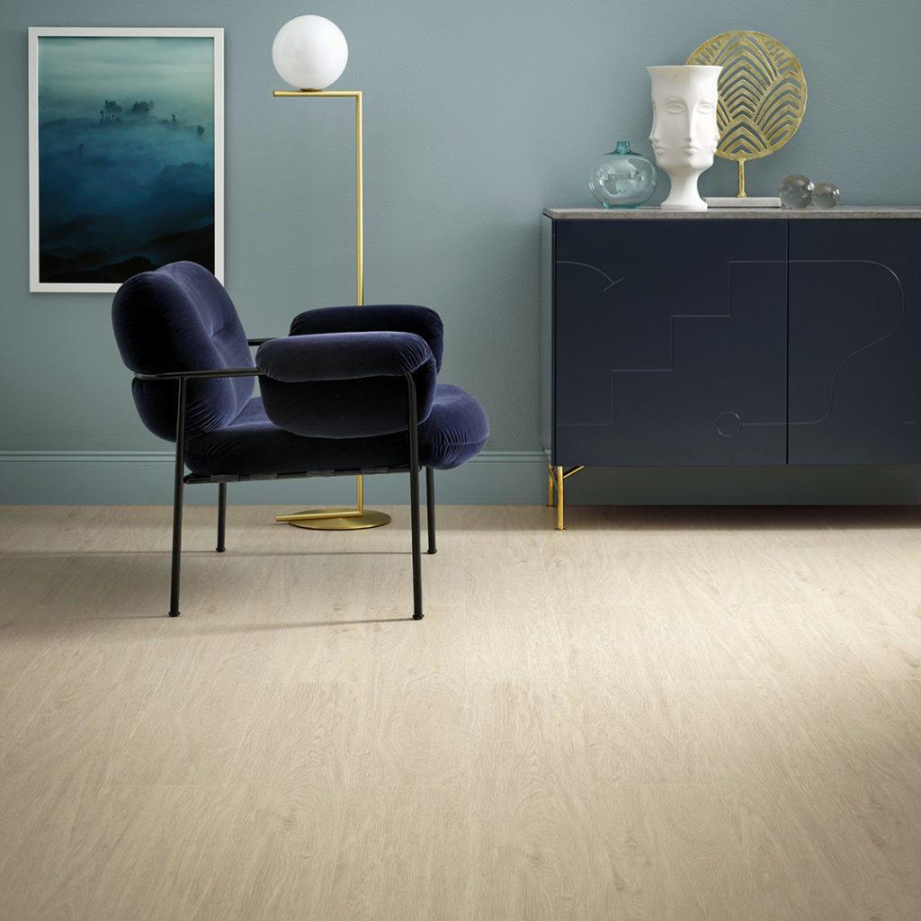 En lilla stol på gulvet foran en lyseblå vegg og en sjenk